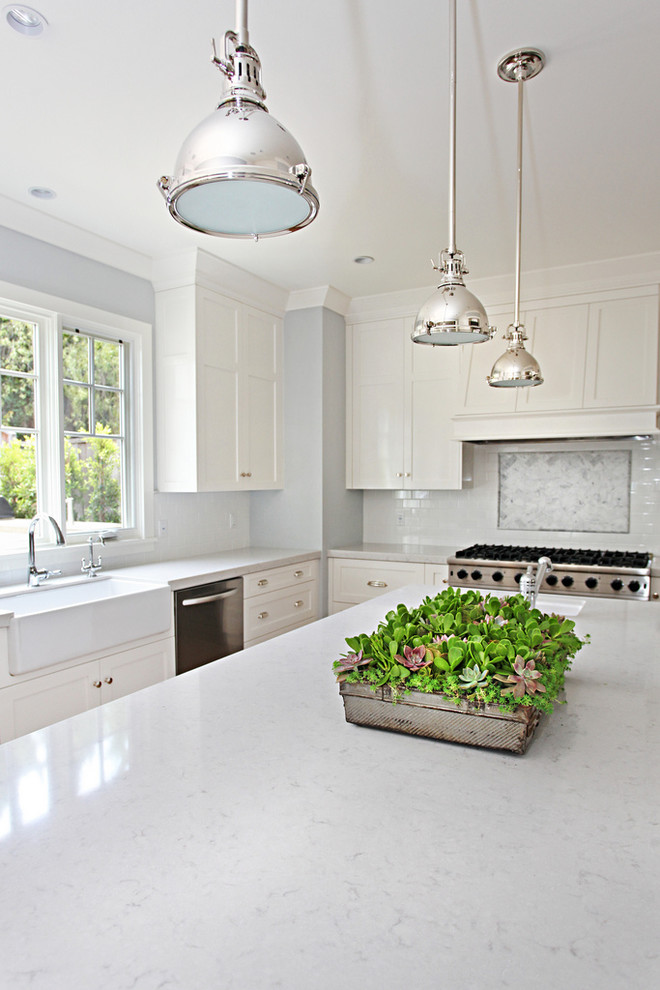Inspiration for a transitional l-shaped open concept kitchen remodel in Orange County with a farmhouse sink, recessed-panel cabinets, white cabinets, quartz countertops, white backsplash, subway tile backsplash and stainless steel appliances