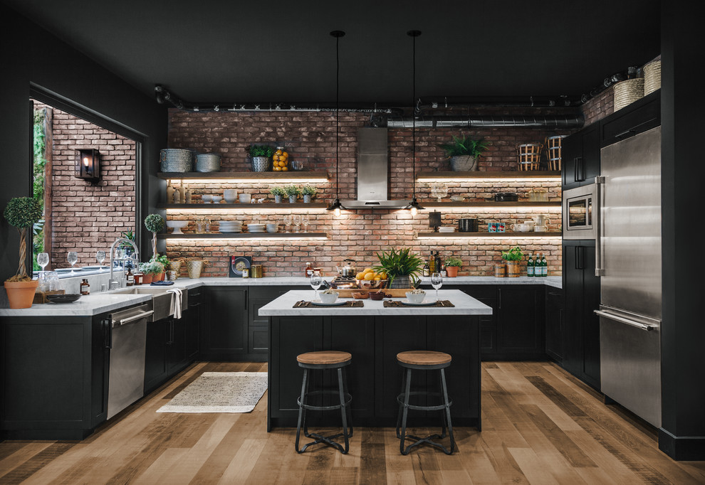 Example of a large urban u-shaped laminate floor and brown floor eat-in kitchen design in Los Angeles with a farmhouse sink, shaker cabinets, black cabinets, red backsplash, brick backsplash, stainless steel appliances, an island and white countertops