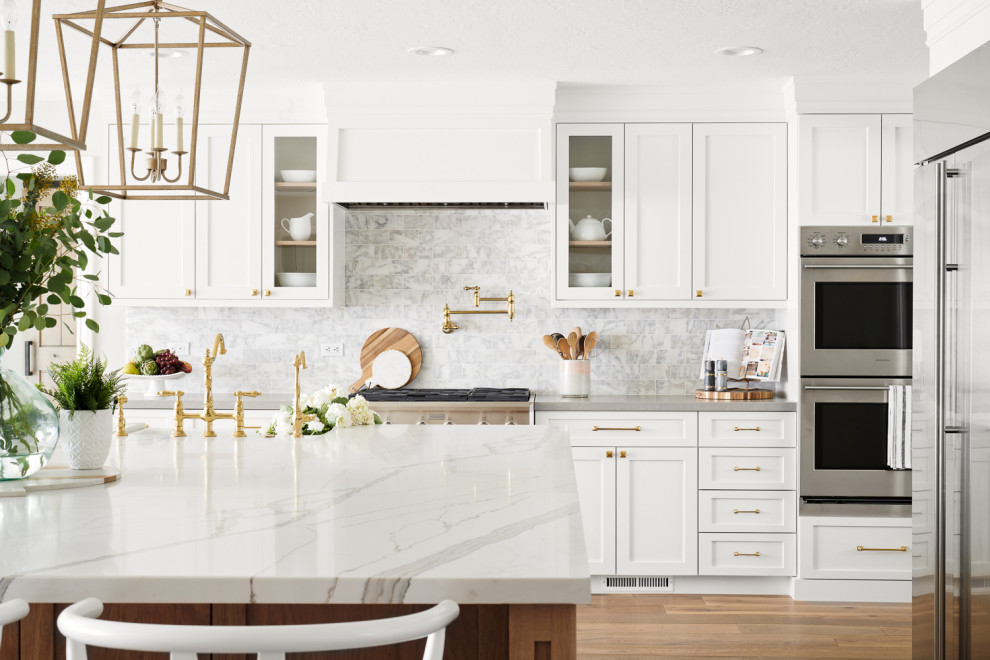 Kitchen - large scandinavian l-shaped light wood floor and beige floor kitchen idea in San Francisco with a farmhouse sink, white cabinets, white backsplash, stainless steel appliances, an island, recessed-panel cabinets, quartzite countertops, marble backsplash and white countertops