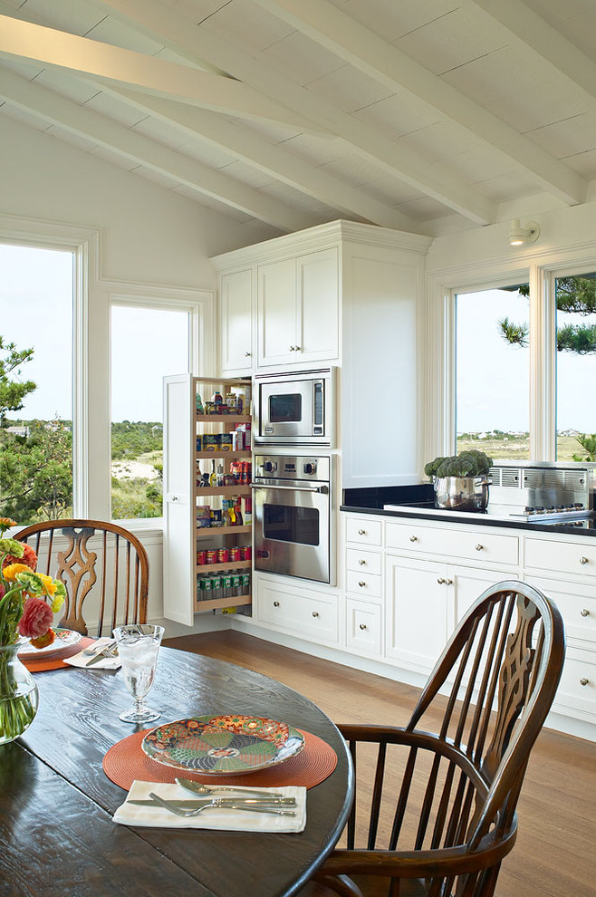 Example of a classic medium tone wood floor eat-in kitchen design in New York with stainless steel appliances, shaker cabinets, white cabinets and an island