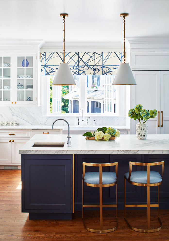 Inspiration for a large transitional l-shaped medium tone wood floor kitchen remodel in New York with white cabinets, white backsplash, an island, white countertops, a farmhouse sink, shaker cabinets, marble countertops, marble backsplash and paneled appliances