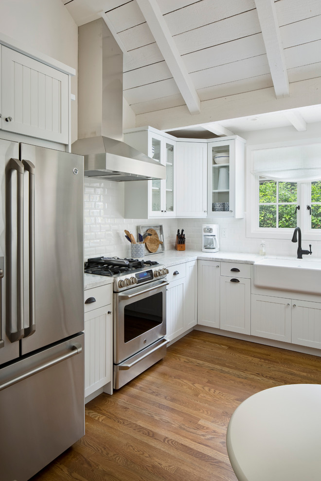 Mid-sized farmhouse l-shaped medium tone wood floor kitchen photo in Other with a farmhouse sink, recessed-panel cabinets, white cabinets, granite countertops, white backsplash, subway tile backsplash, stainless steel appliances and no island