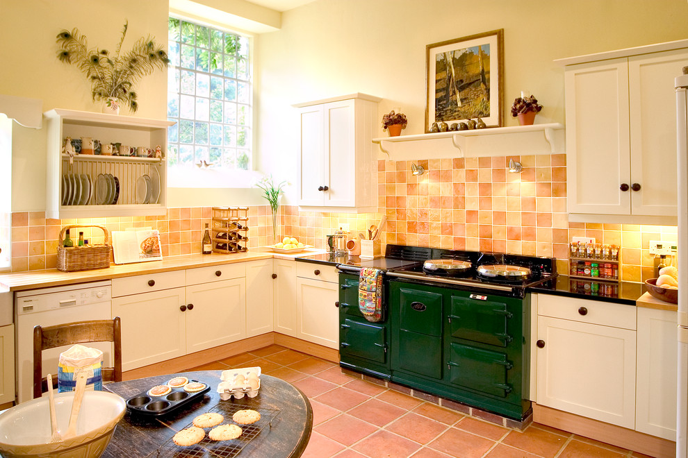 Example of a cottage terra-cotta tile eat-in kitchen design in Other with shaker cabinets, white cabinets, wood countertops, a farmhouse sink, orange backsplash and colored appliances