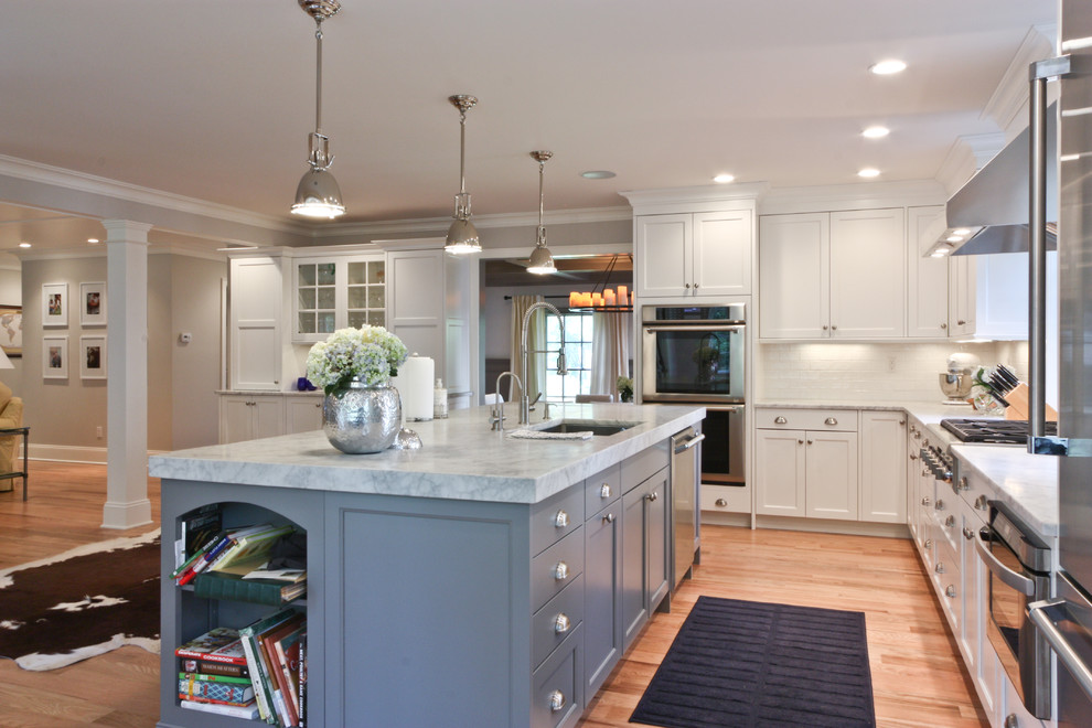 Inspiration for a timeless open concept kitchen remodel in Newark with stainless steel appliances, gray cabinets, recessed-panel cabinets, marble countertops and white backsplash