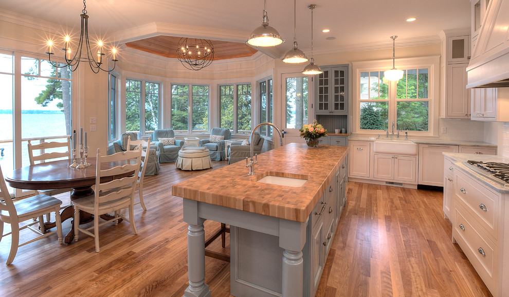 Inspiration for a coastal open concept kitchen remodel in Other with a farmhouse sink, blue cabinets and wood countertops
