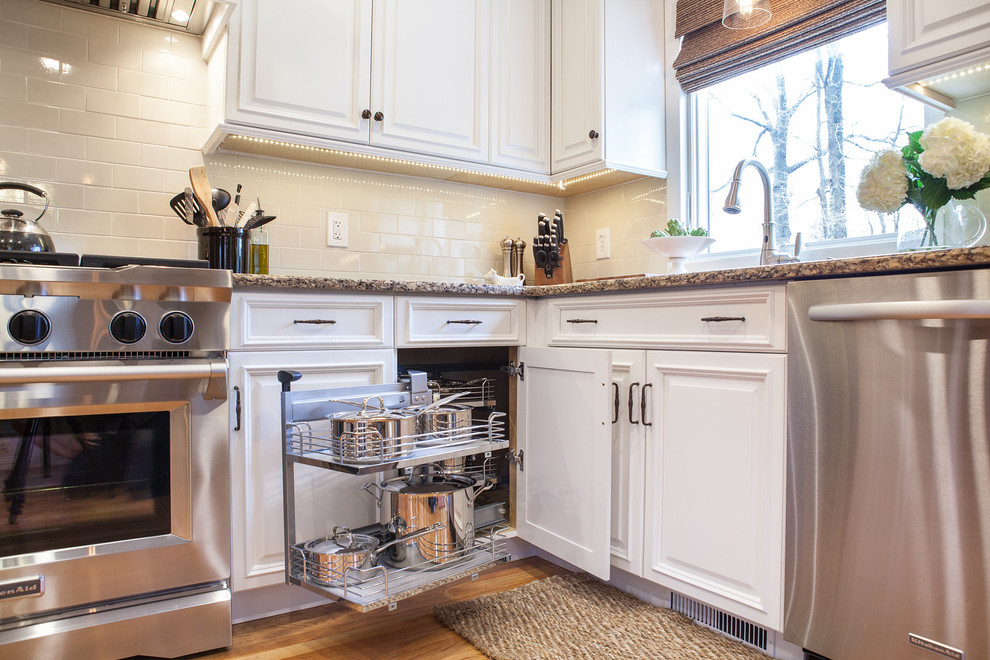 Example of a mid-sized classic u-shaped light wood floor eat-in kitchen design in New York with an undermount sink, raised-panel cabinets, white cabinets, quartz countertops, beige backsplash, subway tile backsplash, stainless steel appliances and a peninsula