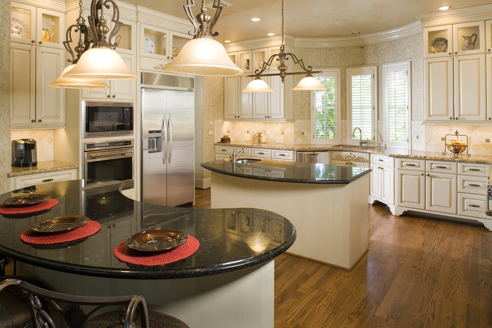 Example of a classic kitchen design in Houston with raised-panel cabinets, beige cabinets, beige backsplash and stainless steel appliances