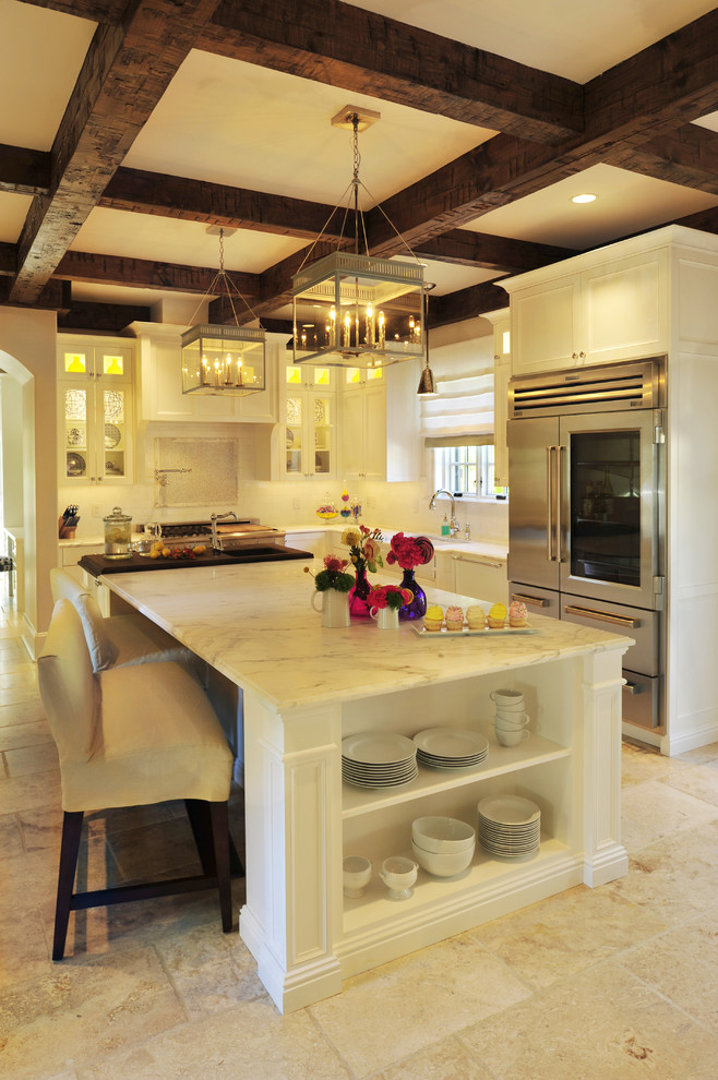 Example of a classic l-shaped kitchen design in Nashville with glass-front cabinets, white cabinets, marble countertops and stainless steel appliances