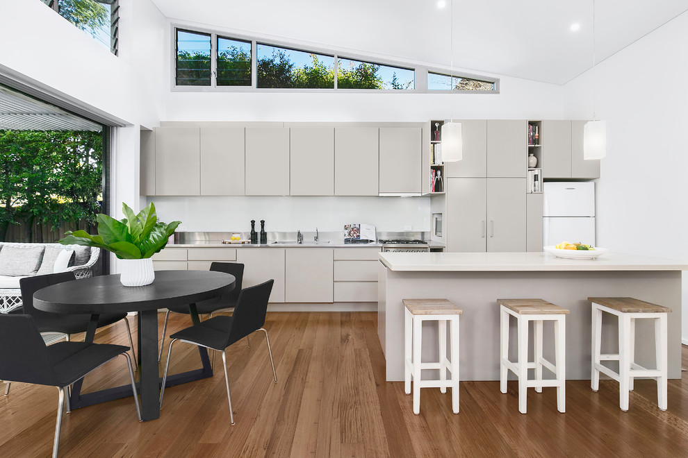 Inspiration for a mid-sized contemporary galley medium tone wood floor and brown floor eat-in kitchen remodel in Sydney with a double-bowl sink, gray cabinets, quartz countertops, white backsplash, glass sheet backsplash, stainless steel appliances, an island, white countertops and flat-panel cabinets