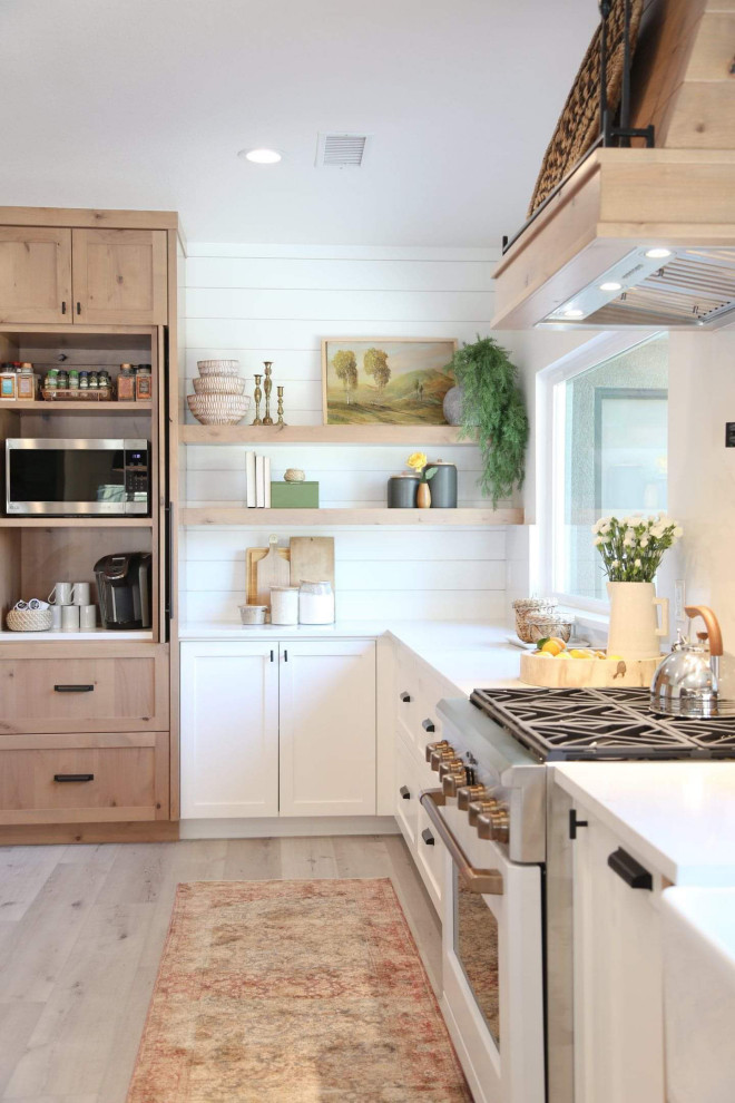 Large transitional l-shaped laminate floor and gray floor kitchen photo in Other with shaker cabinets, white cabinets, quartz countertops, white backsplash, quartz backsplash, white appliances and white countertops