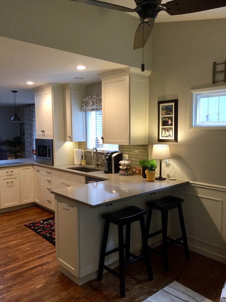 Small u-shaped medium tone wood floor open concept kitchen photo in Portland with an undermount sink, shaker cabinets, white cabinets, quartz countertops, gray backsplash, glass tile backsplash, stainless steel appliances, a peninsula and gray countertops