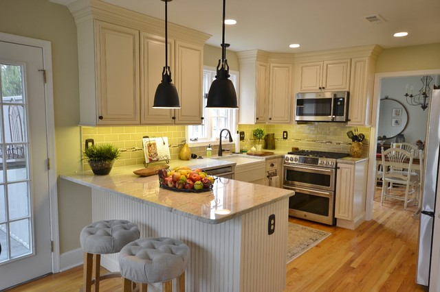 Inspiration for a mid-sized timeless l-shaped light wood floor and brown floor eat-in kitchen remodel in Philadelphia with a farmhouse sink, raised-panel cabinets, white cabinets, granite countertops, beige backsplash, ceramic backsplash, stainless steel appliances and a peninsula