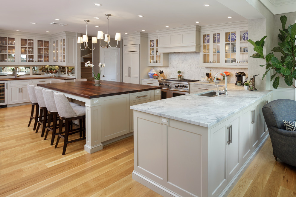 Inspiration for a large timeless u-shaped light wood floor and beige floor enclosed kitchen remodel in Philadelphia with an undermount sink, recessed-panel cabinets, white cabinets, marble countertops, white backsplash, marble backsplash, paneled appliances and two islands