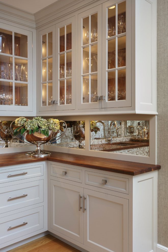 Example of a large classic u-shaped light wood floor and beige floor enclosed kitchen design in Philadelphia with an undermount sink, recessed-panel cabinets, white cabinets, marble countertops, white backsplash, marble backsplash, paneled appliances and two islands