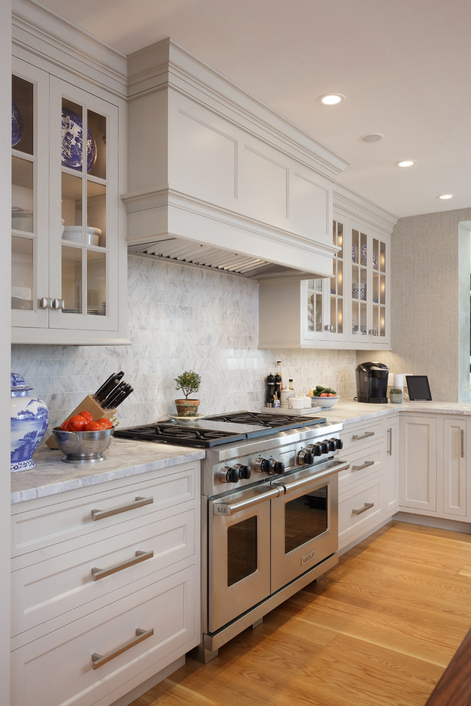 Large elegant u-shaped light wood floor and beige floor enclosed kitchen photo in Philadelphia with an undermount sink, recessed-panel cabinets, white cabinets, marble countertops, white backsplash, marble backsplash, paneled appliances and two islands