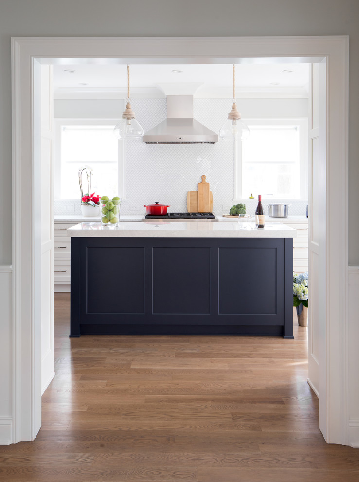 Inspiration for a mid-sized transitional medium tone wood floor eat-in kitchen remodel in New York with an undermount sink, shaker cabinets, white cabinets, marble countertops, white backsplash, stone tile backsplash, stainless steel appliances and an island
