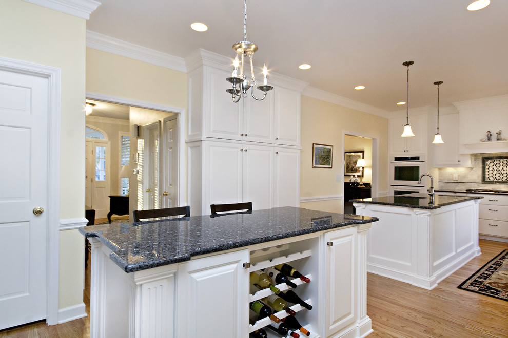 Large elegant l-shaped eat-in kitchen photo in Raleigh with an undermount sink, raised-panel cabinets, white cabinets, granite countertops, white backsplash, subway tile backsplash, white appliances, blue countertops and two islands