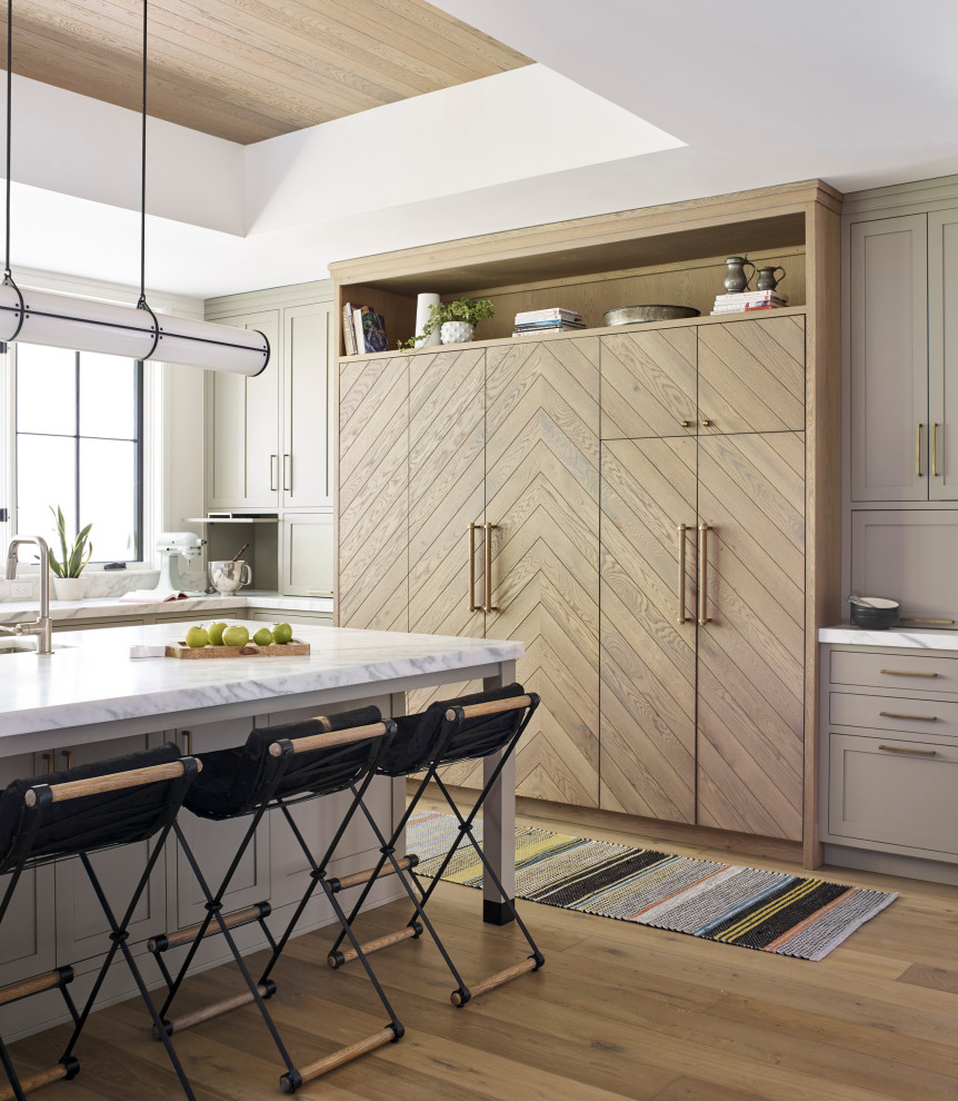 Example of a large transitional l-shaped medium tone wood floor and brown floor open concept kitchen design in New York with an undermount sink, light wood cabinets, marble countertops, white backsplash, marble backsplash, an island, white countertops, flat-panel cabinets and paneled appliances