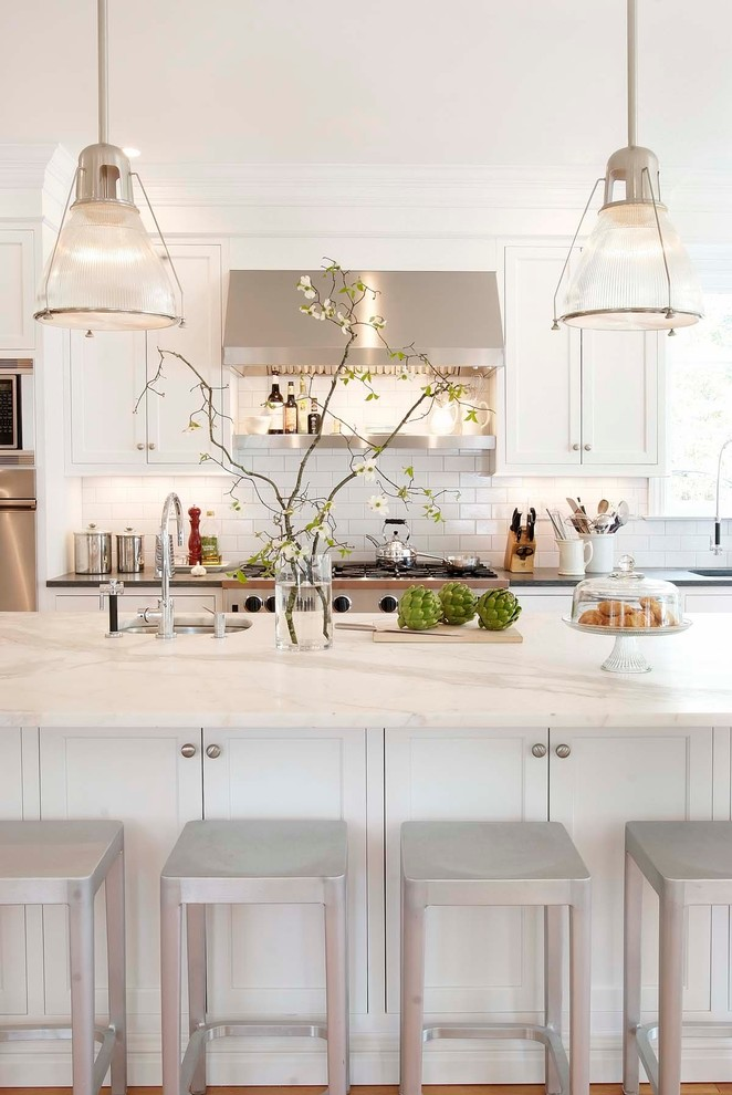 Elegant kitchen photo in New York with stainless steel appliances, marble countertops, recessed-panel cabinets, white cabinets, white backsplash, subway tile backsplash and white countertops