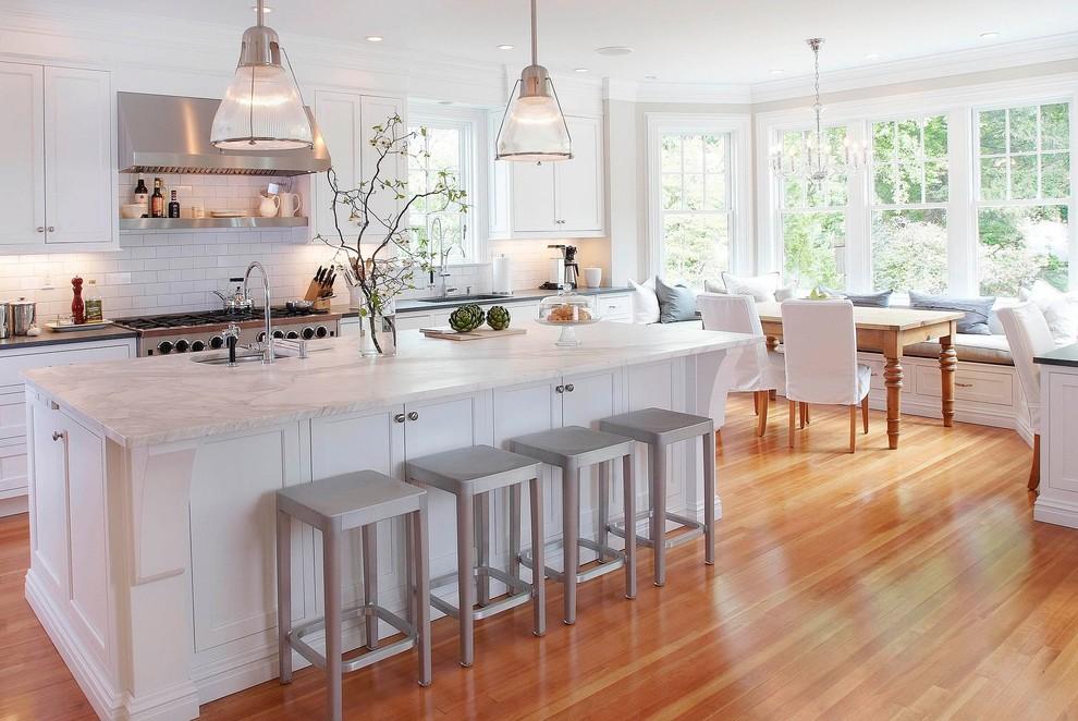 Klassische Wohnküche mit Rückwand aus Metrofliesen, Marmor-Arbeitsplatte, Schrankfronten mit vertiefter Füllung, weißen Schränken, Küchenrückwand in Weiß und weißer Arbeitsplatte in New York