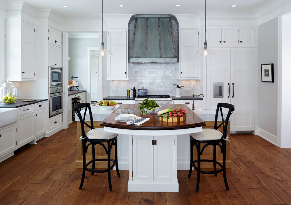 Beach style l-shaped dark wood floor kitchen photo in Minneapolis with a farmhouse sink, shaker cabinets, white cabinets, wood countertops, white backsplash, paneled appliances and marble backsplash