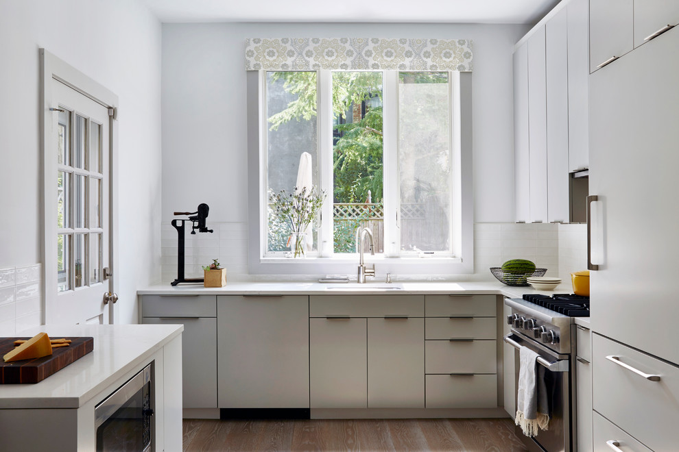 Inspiration for a small transitional u-shaped light wood floor enclosed kitchen remodel in New York with an undermount sink, flat-panel cabinets, gray cabinets, quartz countertops, white backsplash, ceramic backsplash, paneled appliances and no island