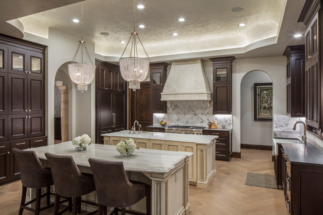 Example of a tuscan light wood floor and beige floor enclosed kitchen design in Austin with a farmhouse sink, recessed-panel cabinets, dark wood cabinets, multicolored backsplash, stainless steel appliances and two islands
