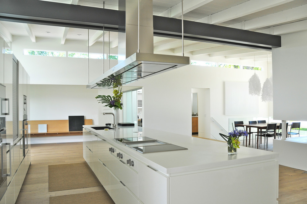 Example of a mid-century modern kitchen design in Denver with stainless steel appliances, white cabinets, solid surface countertops, white backsplash and glass sheet backsplash