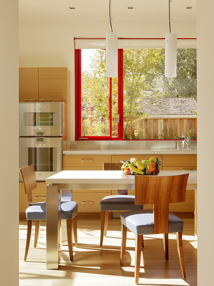 Example of a mid-sized trendy light wood floor eat-in kitchen design in San Francisco with flat-panel cabinets, light wood cabinets and stainless steel appliances