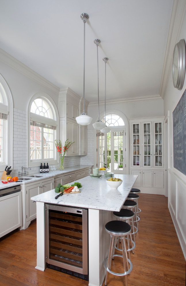 Elegant medium tone wood floor enclosed kitchen photo in New Orleans with shaker cabinets, white cabinets, white backsplash, subway tile backsplash and an island