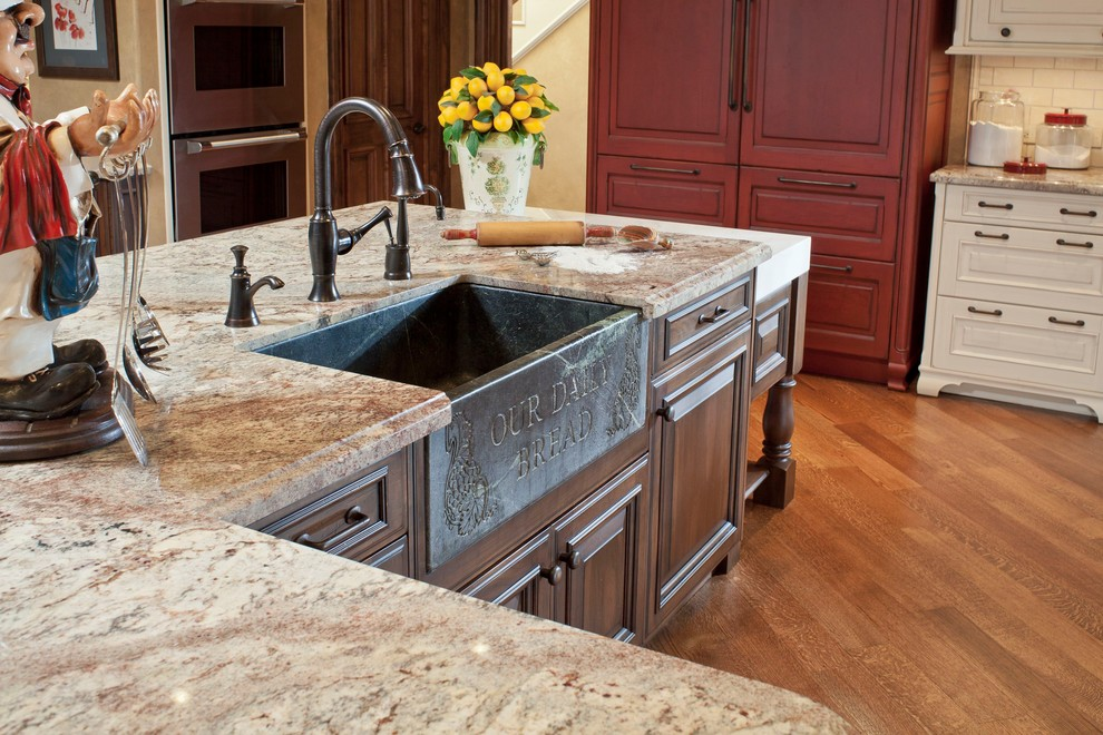Inspiration for a timeless l-shaped light wood floor eat-in kitchen remodel in Houston with a farmhouse sink, white cabinets, granite countertops, white backsplash, paneled appliances and an island