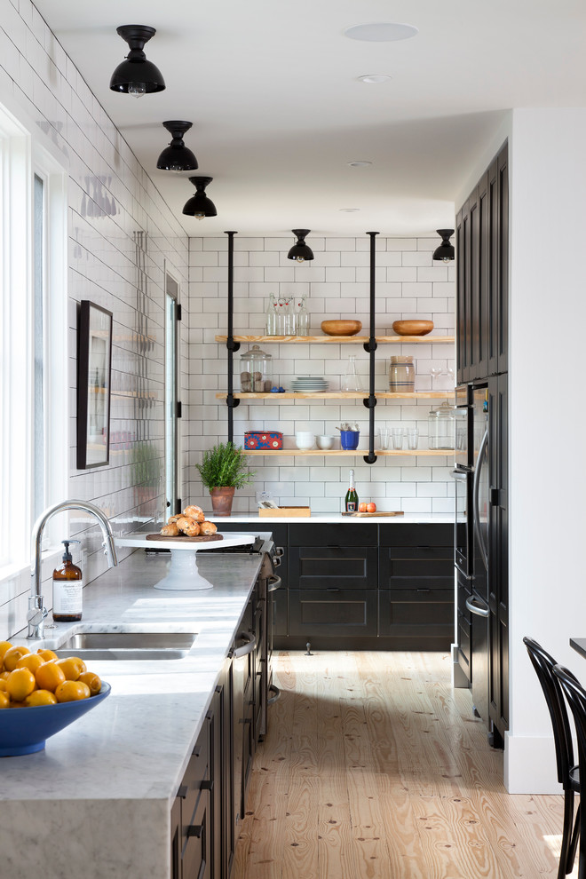 Danish light wood floor eat-in kitchen photo in Austin with no island, an undermount sink, shaker cabinets, marble countertops, white backsplash, subway tile backsplash and stainless steel appliances