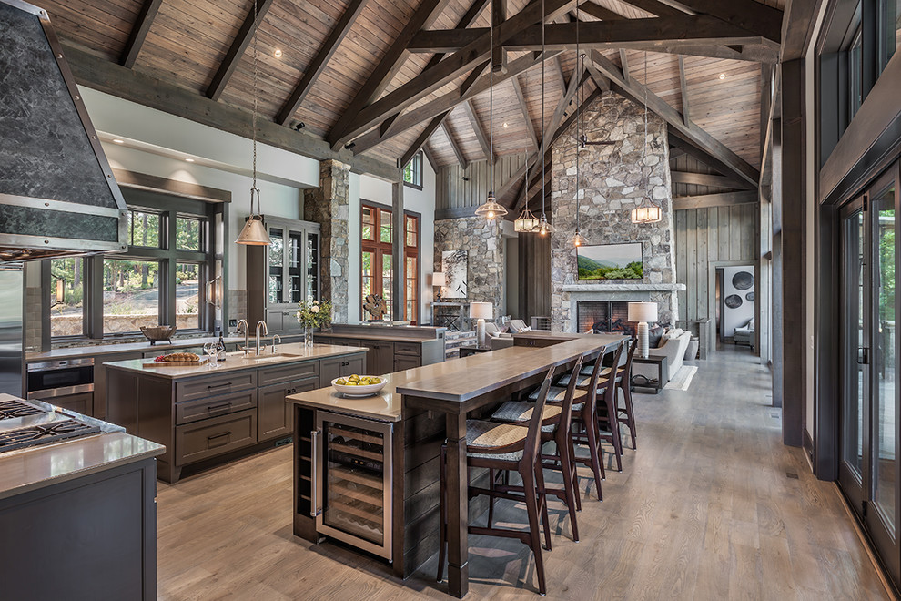 Example of a mountain style light wood floor open concept kitchen design in Other with an undermount sink, glass-front cabinets, brown cabinets, window backsplash, stainless steel appliances, two islands and gray countertops
