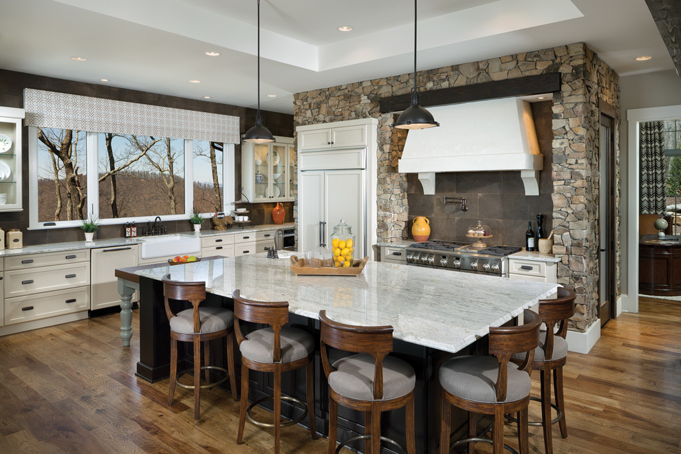 Elegant medium tone wood floor kitchen photo in Other with a farmhouse sink, white cabinets, granite countertops, brown backsplash, ceramic backsplash, paneled appliances, an island and recessed-panel cabinets
