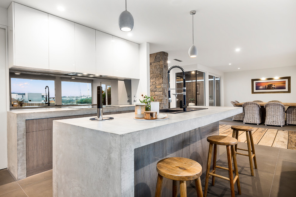 Example of a mid-sized trendy galley limestone floor and gray floor open concept kitchen design in Melbourne with light wood cabinets, concrete countertops, black backsplash, an island, a single-bowl sink, flat-panel cabinets, gray countertops and window backsplash