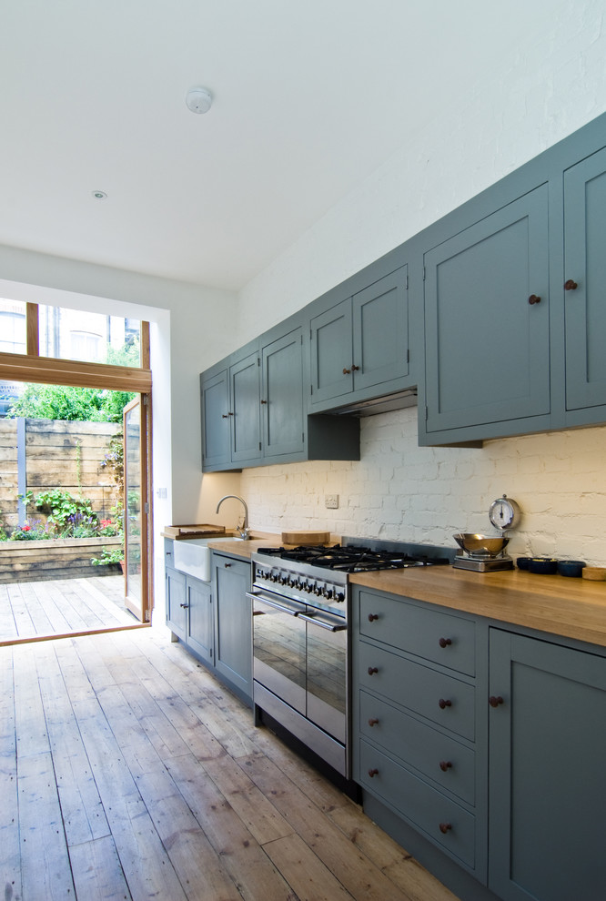 Eat-in kitchen - mid-sized contemporary single-wall medium tone wood floor eat-in kitchen idea in London with wood countertops, white backsplash, a farmhouse sink and blue cabinets