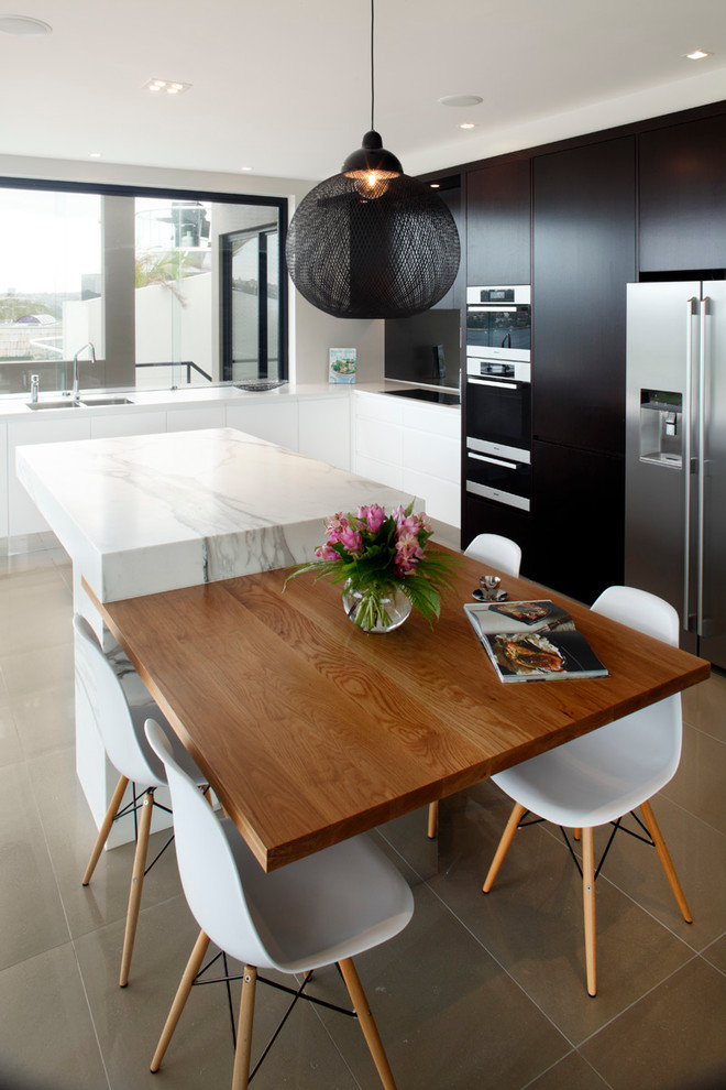 Mid-sized trendy l-shaped porcelain tile enclosed kitchen photo in Sydney with flat-panel cabinets, black cabinets, marble countertops, glass sheet backsplash, stainless steel appliances and an island