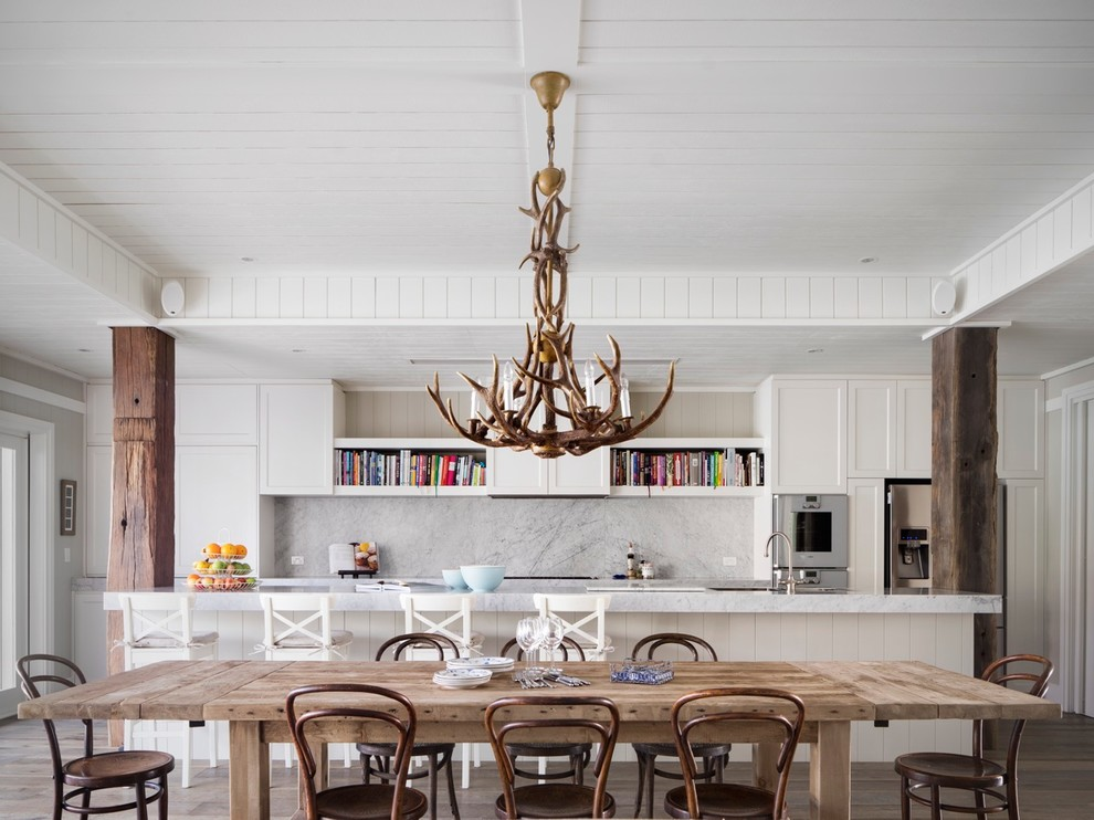 Mid-sized beach style galley eat-in kitchen photo in Sydney with recessed-panel cabinets, white cabinets, marble countertops, stone slab backsplash, stainless steel appliances, an island and white backsplash