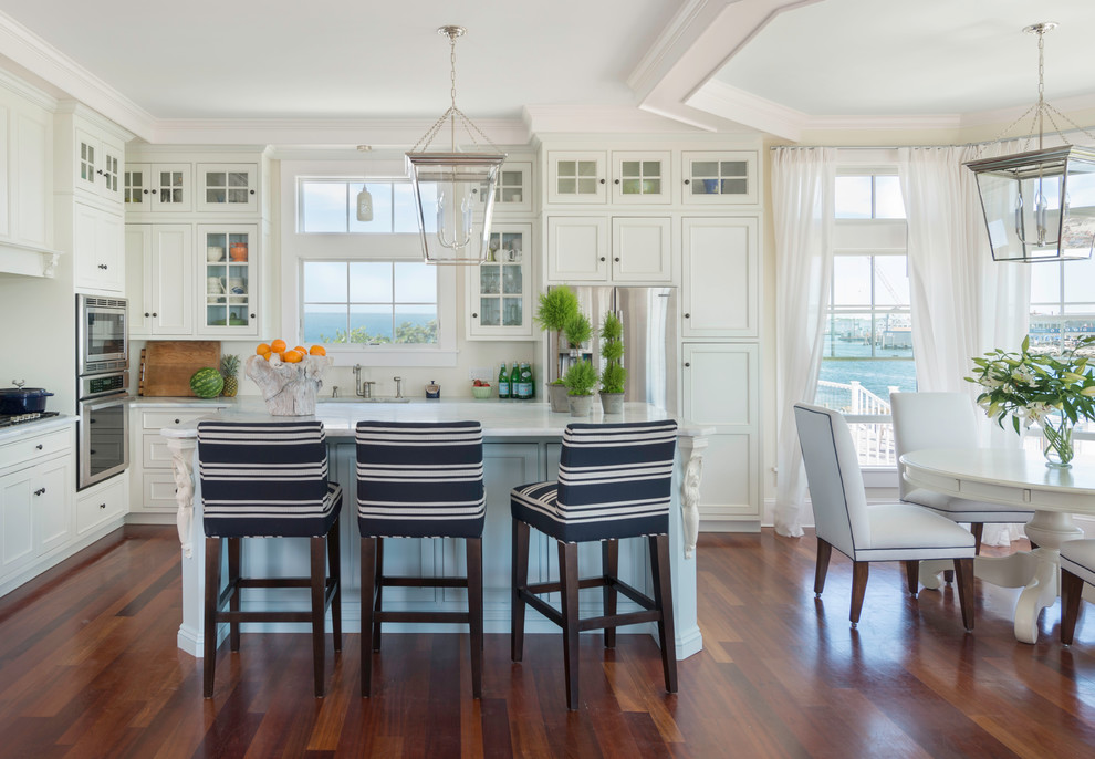 Mid-sized beach style medium tone wood floor eat-in kitchen photo in Providence with recessed-panel cabinets, white cabinets, marble countertops, white backsplash, ceramic backsplash, stainless steel appliances and an island