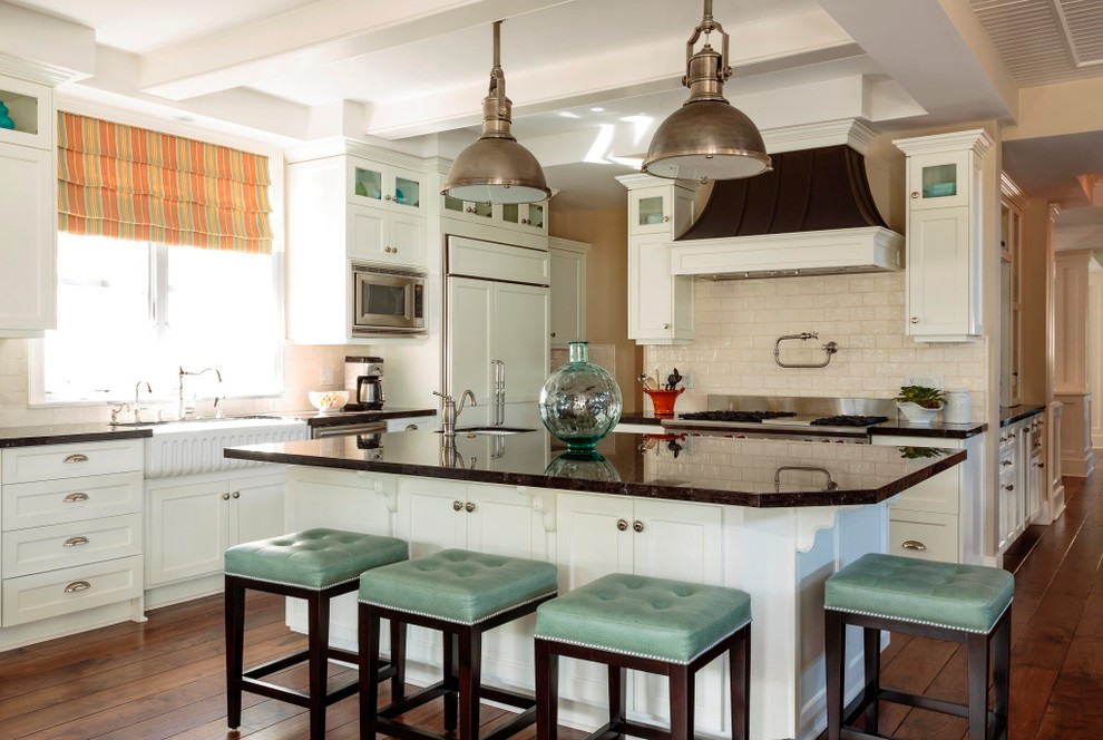 Example of a beach style kitchen design in Los Angeles with a farmhouse sink, shaker cabinets, white cabinets, beige backsplash, subway tile backsplash and paneled appliances