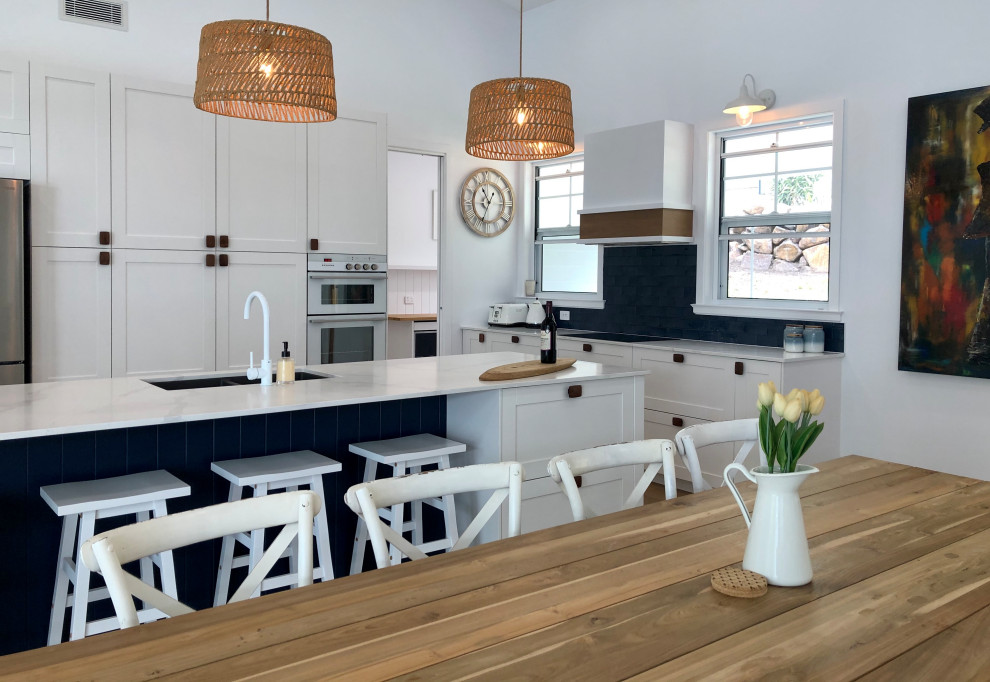Mid-sized beach style l-shaped eat-in kitchen in Gold Coast - Tweed with an undermount sink, shaker cabinets, white cabinets, blue splashback, stainless steel appliances, with island and white benchtop.
