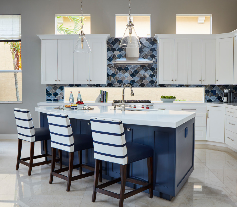 Example of a large beach style l-shaped marble floor and beige floor open concept kitchen design in Miami with an undermount sink, shaker cabinets, white cabinets, blue backsplash, glass tile backsplash, stainless steel appliances and an island