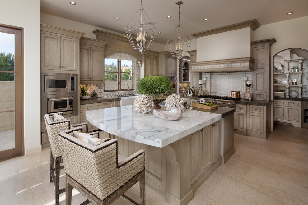 Example of a large beach style light wood floor kitchen design in Orange County with a farmhouse sink, recessed-panel cabinets, light wood cabinets, marble countertops, white backsplash, stainless steel appliances and an island