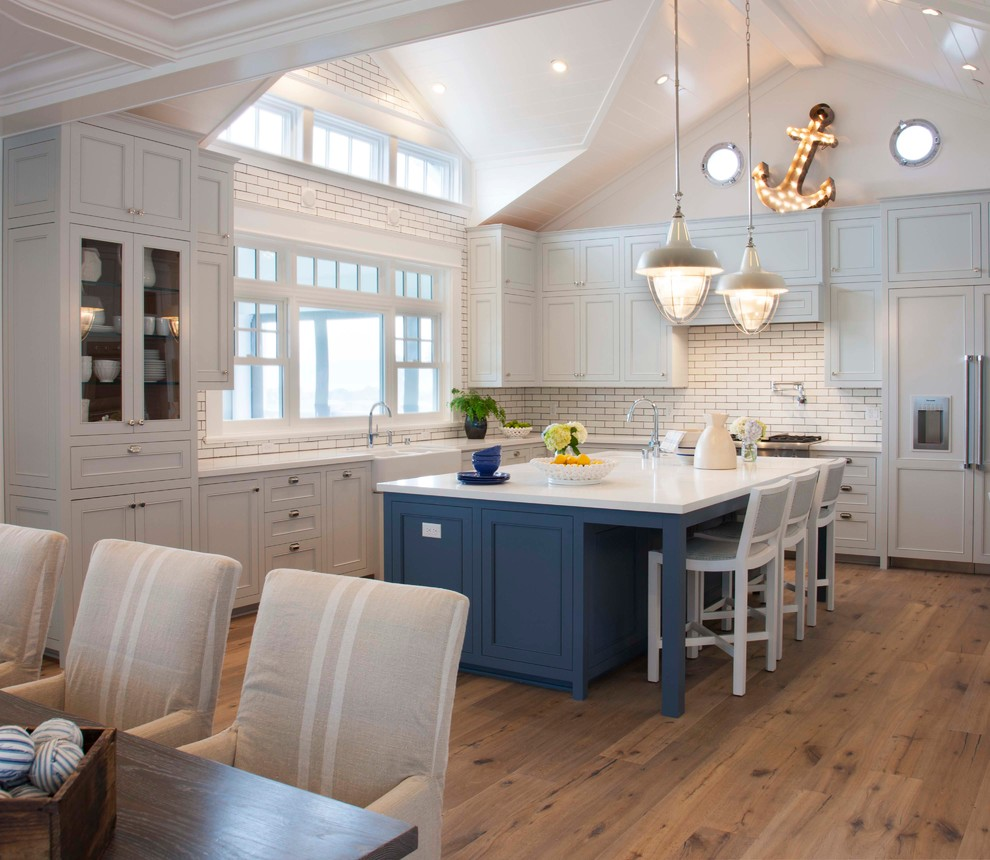 Coastal l-shaped medium tone wood floor and brown floor eat-in kitchen photo in San Diego with a farmhouse sink, recessed-panel cabinets, white cabinets, white backsplash, subway tile backsplash, paneled appliances and an island