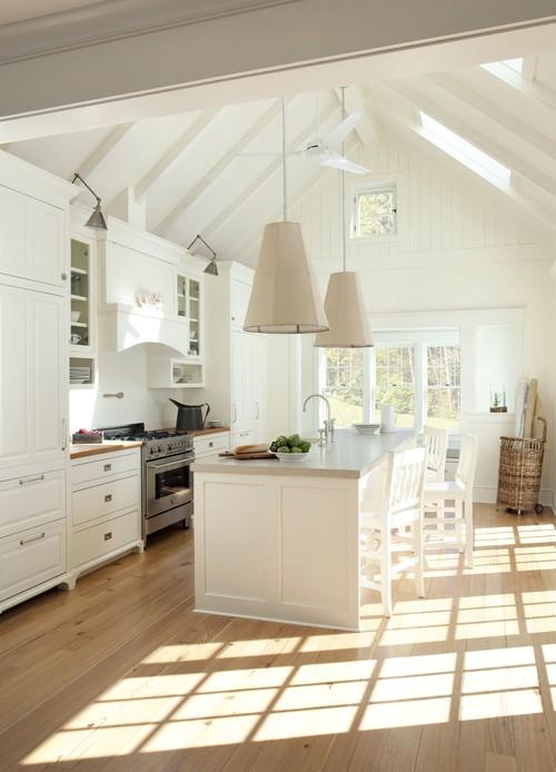 под крышей на мансарде светлая кухня балки крупные светильники остров