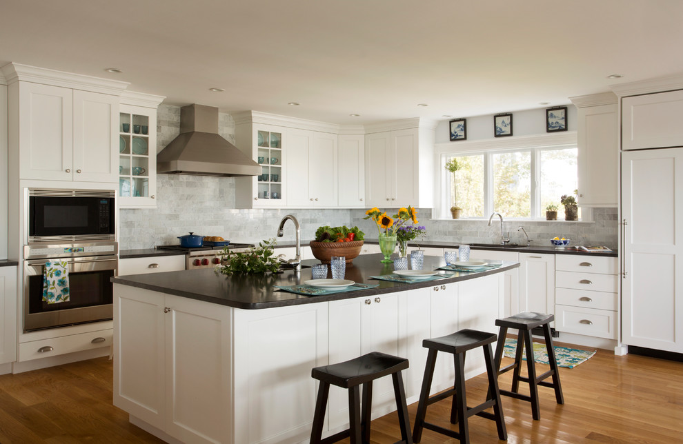 Kitchen - traditional l-shaped light wood floor kitchen idea in Boston with an undermount sink, shaker cabinets, white cabinets, gray backsplash, stainless steel appliances and marble backsplash