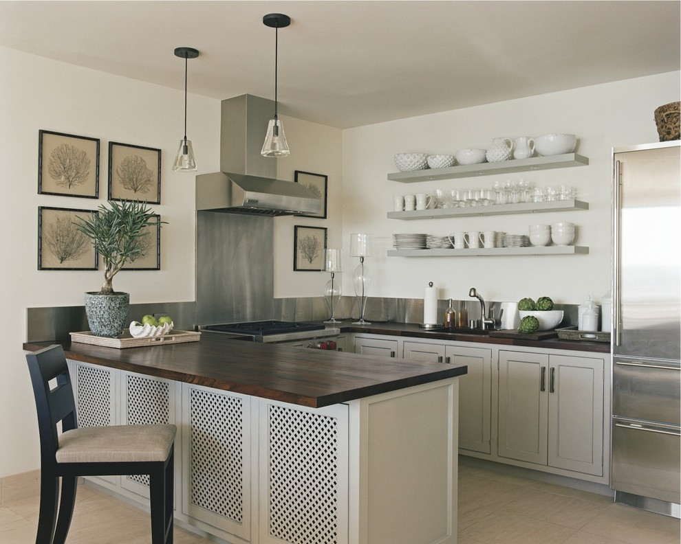 Example of a classic u-shaped kitchen design in New York with stainless steel appliances, wood countertops and open cabinets