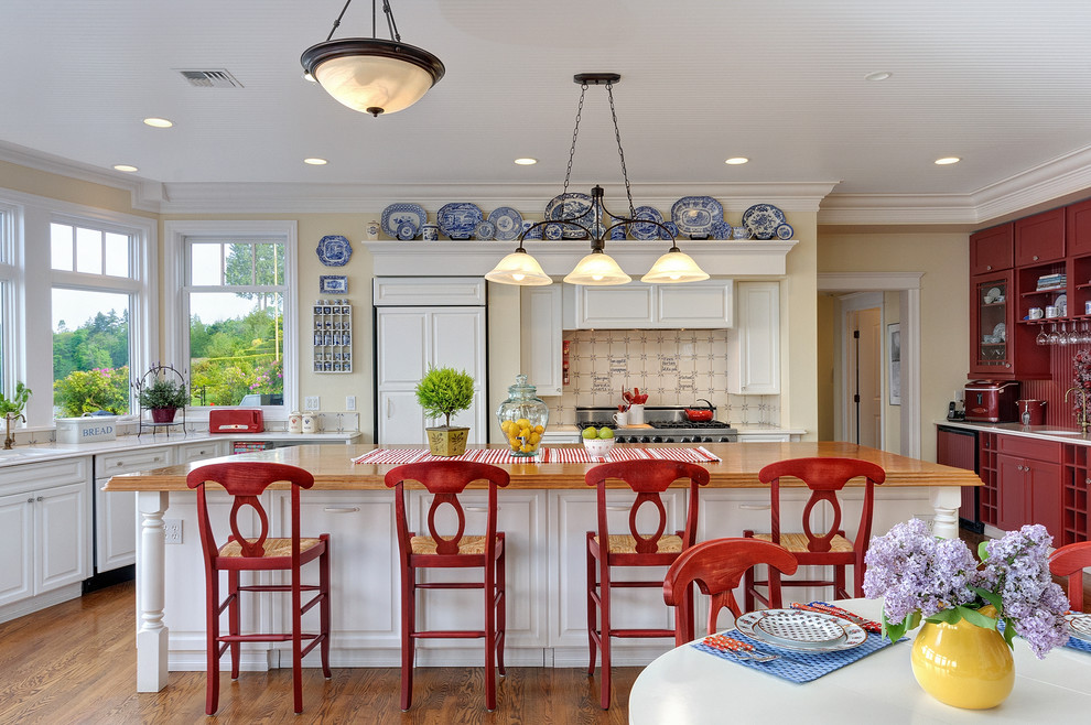Example of a large beach style l-shaped medium tone wood floor eat-in kitchen design in Seattle with wood countertops, paneled appliances, raised-panel cabinets, an island, white cabinets, beige backsplash and ceramic backsplash