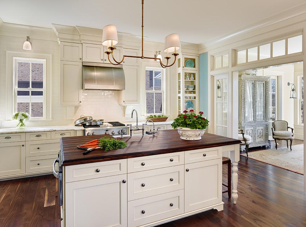 Elegant kitchen photo in Charleston with white cabinets, wood countertops, white backsplash, subway tile backsplash and recessed-panel cabinets