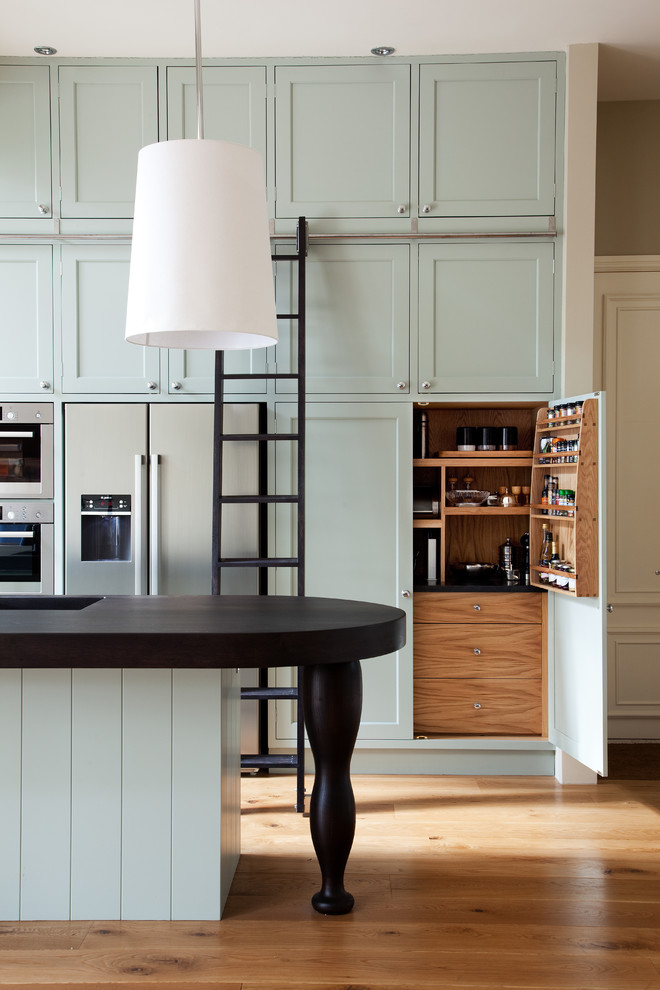 Example of an ornate galley medium tone wood floor kitchen design in London with an integrated sink, shaker cabinets, stainless steel appliances, an island and blue cabinets